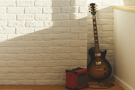 wood texture: White brick interior with guitar, amplifier, blank wall and sunlight. Music concept