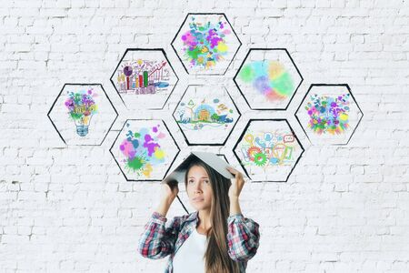 covering cells: Worried young woman covering head with book on brick background with abstract colorful drawings inside cells. Creativity concept Stock Photo