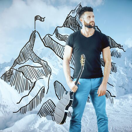 Handsome young man with guitar and creative mountain top sketch on winter landscape background. Leadership and fame concept