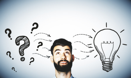idea lamp: Pensive man with drawn question marks and lamp on grey background. Idea concept Stock Photo