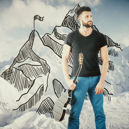 handsome guy: Handsome caucasian guy with guitar and creative mountain top sketch on winter landscape background. Fame concept