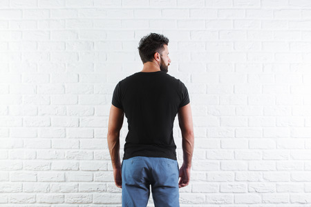 Back view of young male in casual black t-shirt with no print and jeans on white brick wall background. Mock up, Retail concept Imagens
