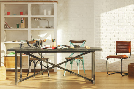 decoration messy: Creative office interior with items on shelves, laptop on table, other items, equipment and sunlight