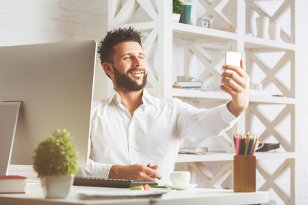 european: Handsome smiling european businessman in modern office taking selfie with smartphone. Leisure concept