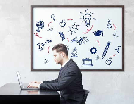 european: Side view of businessman using laptop at workplace with education icons in frame. Knowledge concept