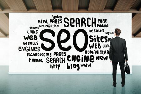 looking at view: Back view of businessman looking at SEO writing on concrete wall in room. Search engine optimization concept. 3D Rendering Stock Photo