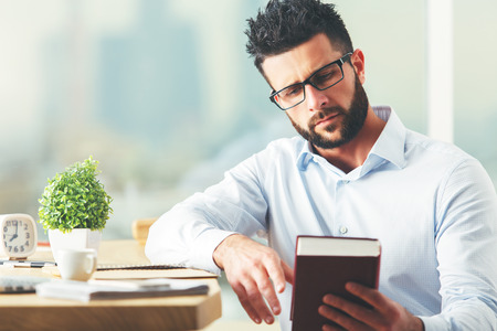 book concept: Close up portrait of attractive european businessman reading book at modern workplace with decorative plant and other items. Knowledge concept