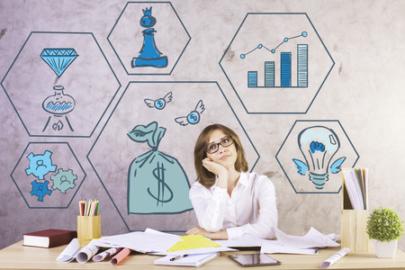working on computer: Attractive white businesswoman at workplace daydreaming about wealth. Business icons in the background