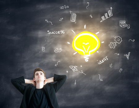 Thoughtful young businessman with light bulb and business icons on chalkboard background. Idea concept