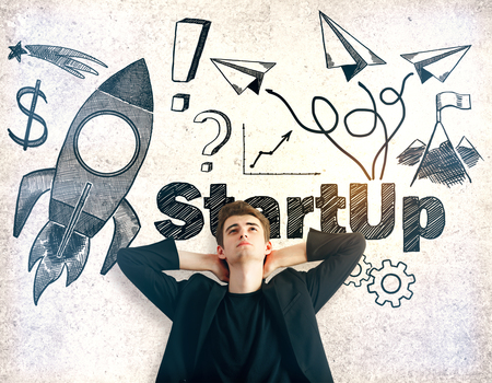young business man: Relaxing young man on textured concrete background with business sketch. Startup concept