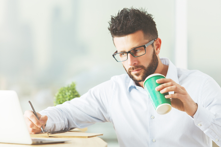 european: Handsome young man with coffee cup in hand working on project at workplace. Work concept