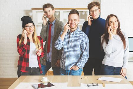 Group of beautiful smiling guys and girls in office talking on their phones all at once. Communication concept Stock Photo