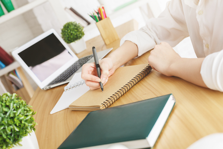 Close up of womans hands writing in spiral notepad placed on wooden desktop with blank laptop screen. Paperwork concept. Mock up