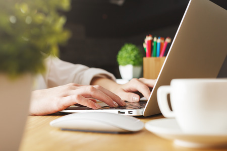 Close up and side view of female hands typing on laptop keyboard placed on wooden desktop with decorative plants and coffee cup