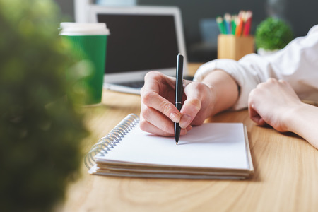 copyspace: Close up of girls hands writing in spiral notepad placed on wooden desktop with blank laptop screen. Paperwork concept. Mock up Stock Photo