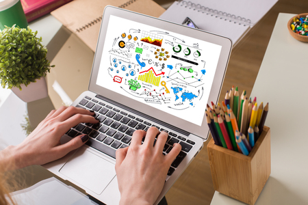 business supplies: Female hands using laptop with colorful business sketch. Workplace with plant, pencil pot and other supplies in the background. Communication concept