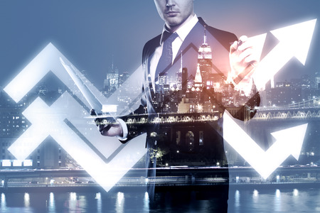 Businessman drawing abstract upward chart arrows on night city background. Success concept. Double exposure