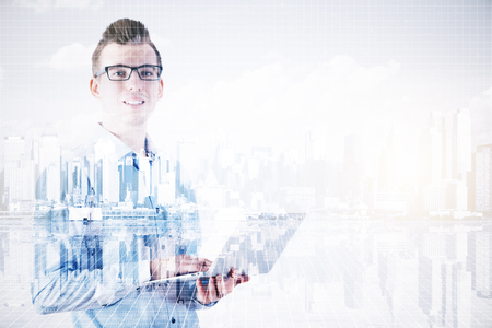 european: Handsome smiling businessman using laptop on abstract city background with copy space. Double exposure. Communication concept