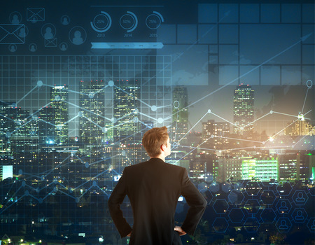 Back view of young businessman looking into the distance on night city and forex chart background. Trading concept