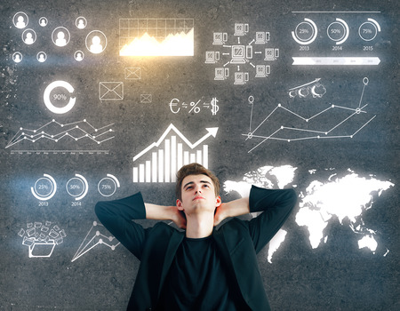 finance concept: Thoughtful man with drawn business charts on dark concrete background. Finance concept Stock Photo