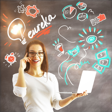 woman laptop: Attractive young woman with laptop in hands on concrete background with eureka exclamation and drawings. Genius concept