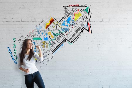 Mujer joven feliz con el bosquejo de colores en el fondo de ladrillo. idea de concepto de éxito