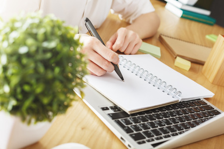 Businesswoman writing in notepad placed on laptop keyboard at workplace with plant and supplies. Project concept Stock Photo