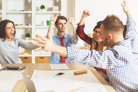 Happy young caucasian people celebrating success at workplace. Entrepreneurship concept