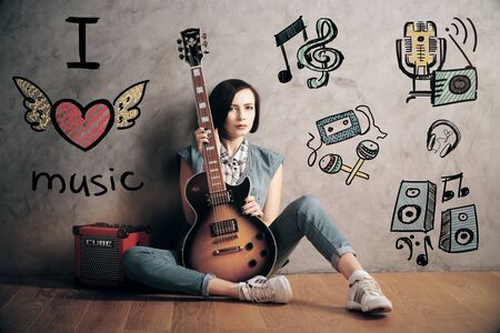 attractive woman: Attractive young woman with guitar and amplifier sitting on the floor in interior with sketch on concrete wall. Music lover concept Stock Photo