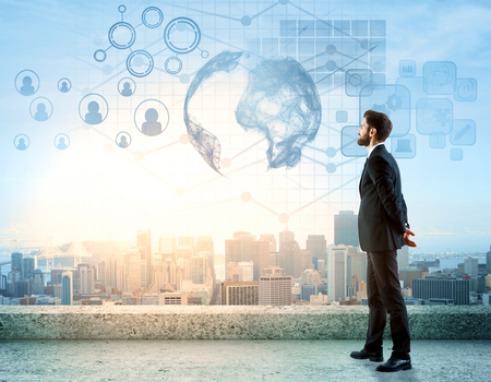 Side view of handsome young man standing on rooftop with digital charts, globe, HR and other icons. City view background. International business concept Standard-Bild