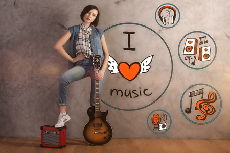 attractive woman: Attractive young woman with guitar and foot on amplifier standing in interior with sketch on concrete wall. Music lover concept