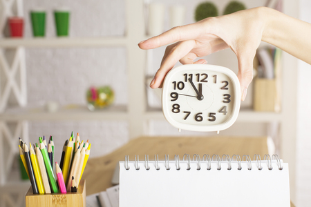 Womans hand holding white clock bove empty spiral notepad