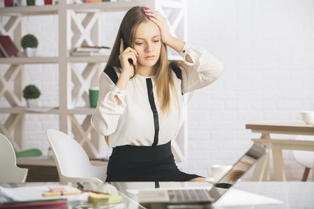 1 person: Stressed young woman at workplace talking on the phone. Business challenge concept