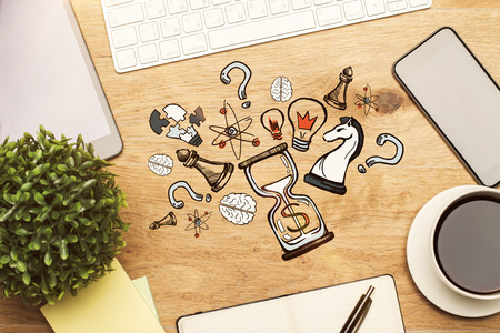 table top: Top view of wooden office desktop with coffee cup, blank smartphone, plant, keyboard, supplies and creative sketch. Business strategy concept