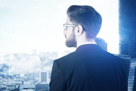 personas pensando: Vista posterior del pensamiento joven empresario en el fondo de la ciudad. concepto de la investigación