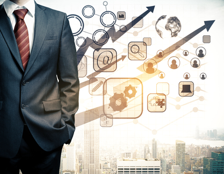 Man in suit with abstract digital business charts, globe, arrows, HR and other icons on city background