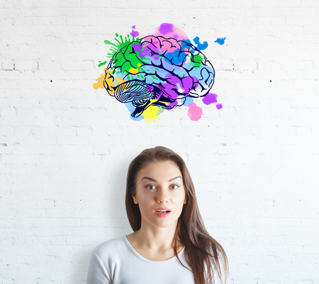Surprised young woman on white brick background with colorful brain sketch. Creative mind concept Stock Photo