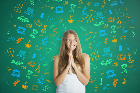 Cheerful young woman with hands put together on green background with science icons. Education concept