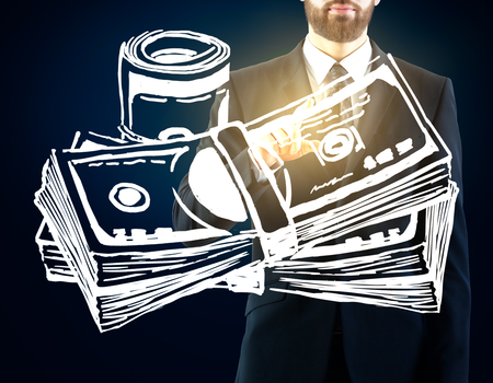 creative money: Businessman pointing at creative cash sketch in dark background. Money concept