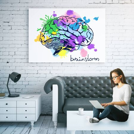 girl using laptop: Attractive young woman sitting on coffee table and using laptop in interior with colorful brain sketch. Brainstorm concept. 3D Rendering
