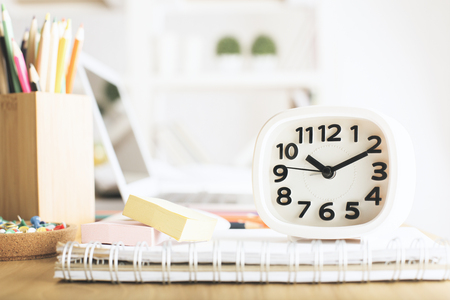 laptop: Close up of white clock placed on office desk with spiral notepad stickers, pencils, blurry laptop in the background and other items Stock Photo