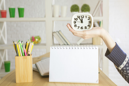 Girls hand holding clock above empty notepad. Mock up