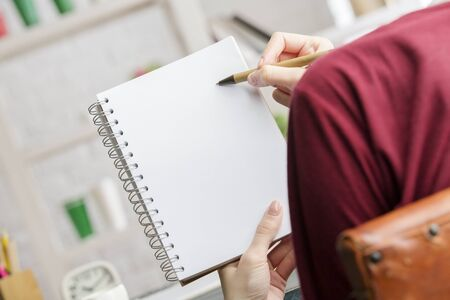 Close up of female hands holding and writing in empty spiral notepad next to office workplace with other supplies and coffee cup. Copy space Stock Photo