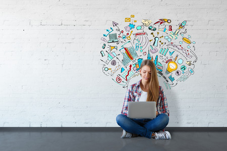 communication: Cheerful young woman sitting on floor and using laptop in white brick interior with business sketch on wall. Education concept. 3D Rendering Stock Photo