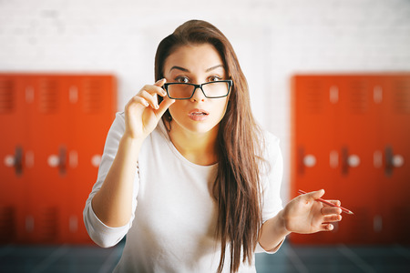 woman looking up: Portrait of surprised young woman in interior with lockers. 3D Rendering Stock Photo