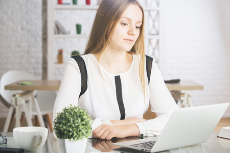 white work: Portrait of attractive young caucasian woman using laptop computer at workplace. Technology and communication concept