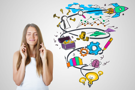 Happy young female with crossed fingers on light background with colorful business sketch. Successful startup concept