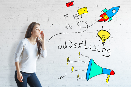 Side view of whispering woman on white brick background with colorful drawings. Advert concept Banco de Imagens