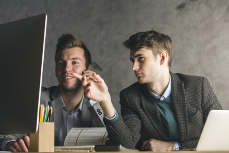 project: Two handsome young businessmen talking on phone and using computer at workplace. Teamwork, communication and work concept