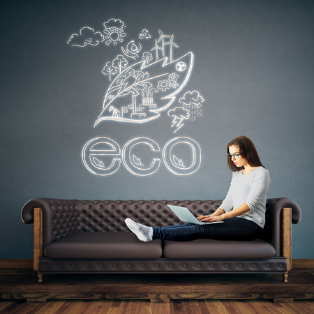 attractive woman: Attractive young woman using laptop while sitting on leather sofa in interior with eco sketch on wall. Environment concept. 3D Rendering